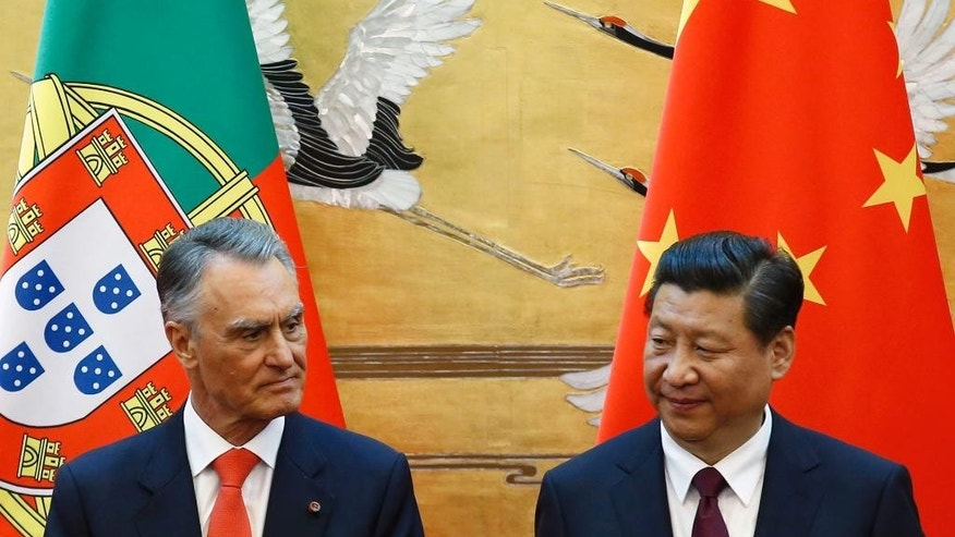 FILE - In this May 15, 2014, file photo, Portugal's President Anibal Cavaco Silva, left, and China's President Xi Jinping attend a signing ceremony at the Great Hall of the People in Beijing. When two Chinese companies appeared among the bidders to buy a troubled Portuguese bank this year, its staff took heart. They believed the potential buyers would do what Chinese investors are increasingly doing in Europe: save badly needed jobs and invest in expanding the business. (Kim Kyung-hoon/Pool Photo via AP)
