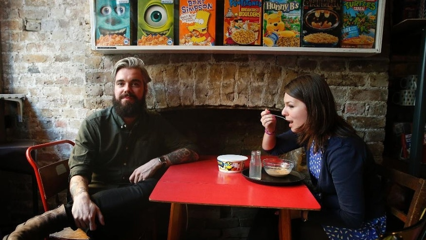 "Alan Keery one of the twin brothers who developed and own the Cereal Killer Cafe in  Brick Lane, London talks to the Associated Press at the cafe, as customer Melanie Wolstenholme eats a late afternoon bowl of cereal, on  Wednesday, Sept. 30, 2015. The Cereal Killer Cafe has drawn both derision and big crowds since it opened nine months ago, offering a cornucopia of flakes, pops and puffs from about 3 pounds ($4.50) a bowl. Now it has attracted the ire of anti-gentrification protesters, who last week surrounded the business with flaming torches and scrawled ""scum"" on its windows as customers sheltered in the basement.  (AP Photo/Alastair Grant)"