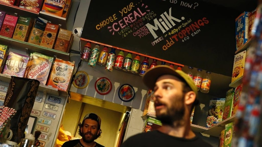 "A member of staff of the Cereal Killer Cafe helps point out to a customer the range of cereals available from US favourites to European gluten free organics at the cafe in Brick Lane,  London, Wednesday, Sept. 30, 2015. The Cereal Killer Cafe has drawn both derision and big crowds since it opened nine months ago, offering a cornucopia of flakes, pops and puffs from about 3 pounds ($4.50) a bowl. Now it has attracted the ire of anti-gentrification protesters, who last week surrounded the business with flaming torches and scrawled ""scum"" on its windows as customers sheltered in the basement.  (AP Photo/Alastair Grant)"