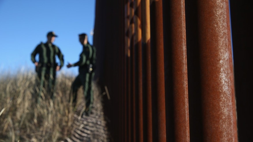 NOGALES, AZ - DECEMBER 09:  U.S. Border Patrol agents talk next to the U.S.-Mexico border fence on December 9, 2014 near Nogales, Arizona. With increased manpower and funding in recent years, the Border Patol has seen the number illegal crossings and apprehensions of undocumented immigrants decrease in the Tucson sector. Agents are waiting to see if the improved U.S. economy and housing construction will again draw more immigrants from the south.  (Photo by John Moore/Getty Images)