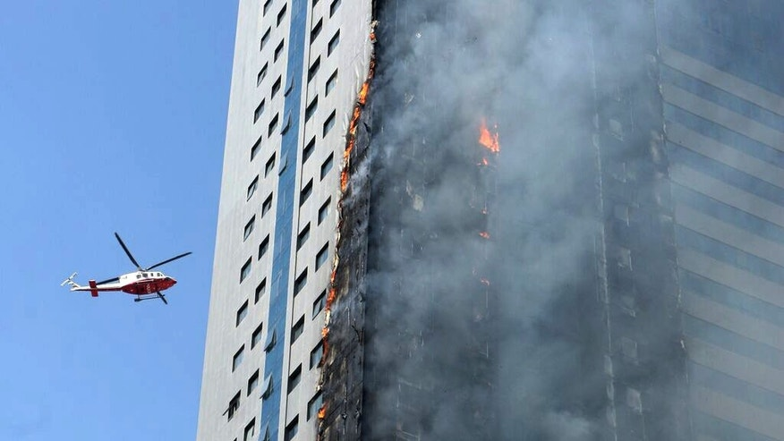 A helicopter hovers over a skyscraper which caught fire in Sharjah, United Arab Emirates, Thursday, Oct. 1, 2015. It was not immediately clear if there were any casualties. The Sharjah civil defense directorate had no immediate comment. (AP Photo)