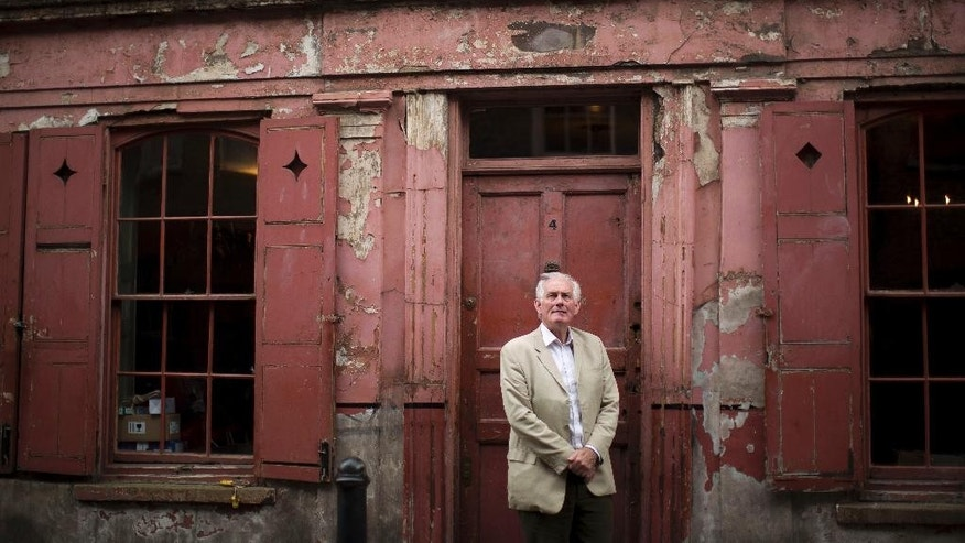 In this Sept. 15, 2015 photo, historian and local resident Dan Cruickshank poses for a portrait outside a Georgian house from the early 18th century on Princelet Street in Spitalfields, where the facade has been kept in a period style so it can be used for location filming purposes in east London. The layering of migrants over centuries, like strata in rock, tells a story vital for Europe to remember as it struggles with new flows of people seeking sanctuary and fresh starts. (AP Photo/Matt Dunham)