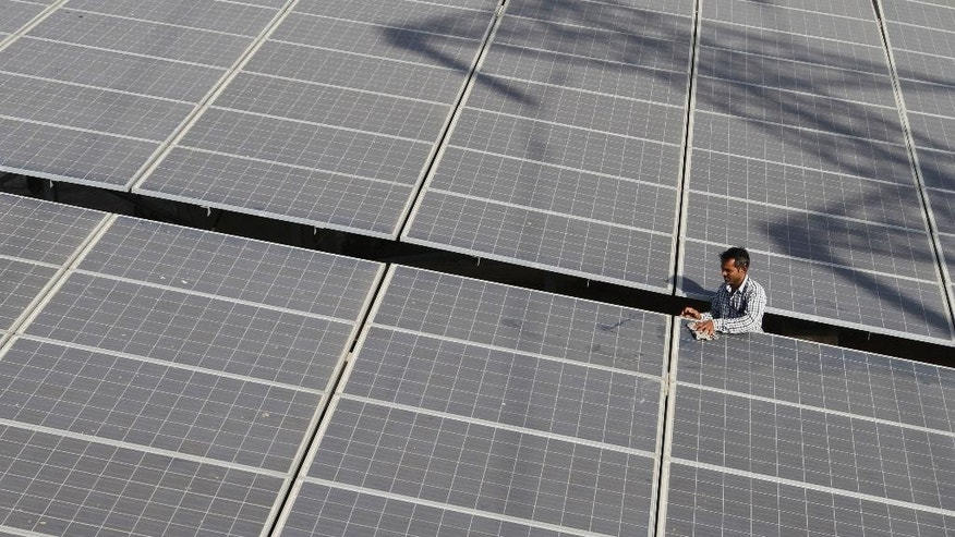 In this Oct. 1, 2015 photo, an Indian man cleans solar panels installed on rooftop in Ahmadabad, India. As the last major economy to submit a target for a global climate pact, India is pledging to reduce the intensity of its carbon emissions and boost the share of electricity produced from sources other than fossil fuels to 40 percent by 2030.  (AP Photo/Ajit Solanki)