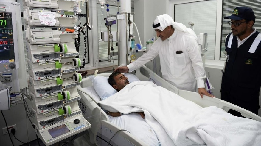 In this Tuesday, Sept. 29, 2015 photo provided by the Saudi state news agency Saudi Press Agency (SPA), an official from the Saudi Health Ministry talks to a victim who was injured in Thursday's stampede during the hajj pilgrimage in Mina, as he visits a hospital in Mecca, Saudi Arabia. Riyadh has said that more than 760 pilgrims died in the stampede near Mecca, the worst disaster to strike the annual pilgrimage in a quarter-century. (Saudi Press Agency via AP)