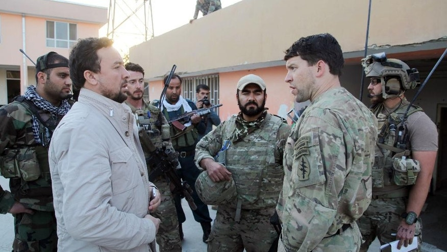 "Kunduz chief of police, Mohammad Qasim Jangalbagh, left, talks to U.S. and Afghan special forces in Kunduz city, north of Kabul, Afghanistan, Thursday, Oct. 1, 2015. An Afghan official says government forces have retaken the strategic northern city of Kunduz (KUHN'-dooz), which was seized by the Taliban on Monday. The spokesman says it could take some days to ""clear the city,"" but that Taliban forces have retreated. He says about 200 Taliban fighters have been killed. (AP Photo)"