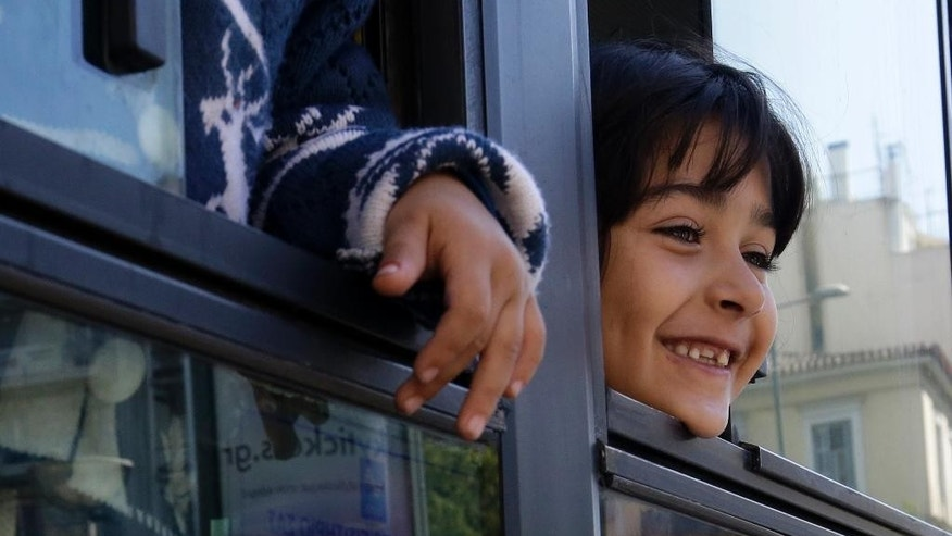A girl looks out of a bus window as she leaves with her family from Victoria square, where hundreds migrants and refugees stay temporarily before trying to continue their trip to more prosperous northern European countries, in Athens on Thursday, Oct. 1, 2015. Authorities in Greece have reopened a disused Galatsi Olympic Hall as police escorted buses carrying about 500 people, mostly from Syria and Afghanistan. (AP Photo/Thanassis Stavrakis)