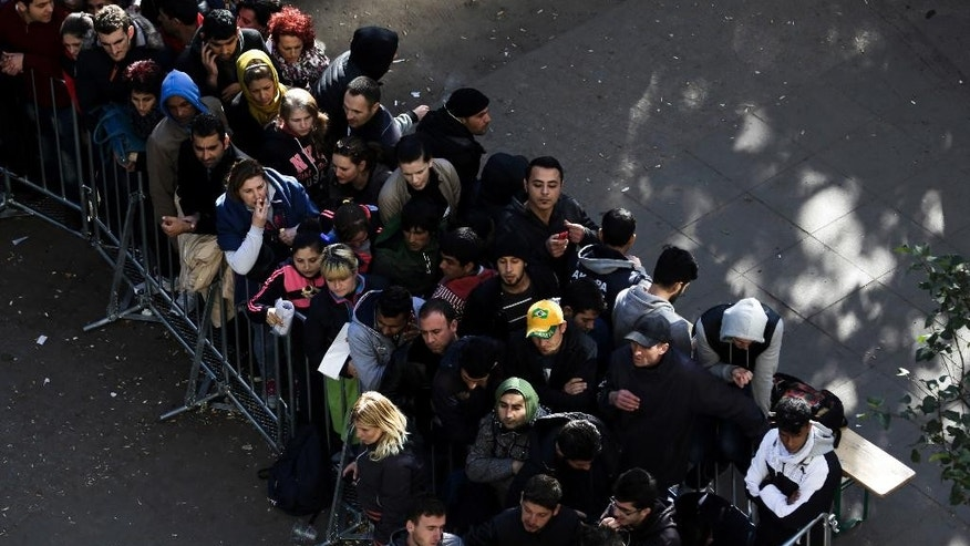 Migrants and refugees wait in a line for their registration at central registration center for refugees and asylum seekers LaGeSo (Landesamt fuer Gesundheit und Soziales - State Office for Health and Social Affairs) in Berlin, Germany, Thursday, Oct. 1, 2015. (AP Photo/Markus Schreiber)