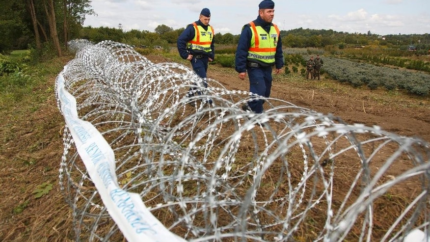 Hungarian police officers patrol the area at the temporary border fence positioned at the green border between Hungary and Croatia at Zakany, 234 km (145 miles) southwest of Budapest, Hungary, Wednesday, Sept. 30, 2015. (Gyorgy Varga /MTI via AP)