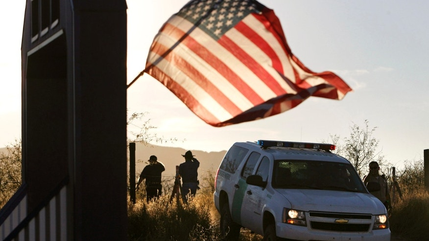 FILE - In this Dec. 15, 2010, file photo, an American flag on a nearby resident's home waves in the breeze near a U.S. Border Patrol truck blocking the road leading to a search area near where agent Brian Terry, 40, was killed northwest of Nogales, Ariz. Two men charged with murder in the death of  agent Terry that revealed the bungled gun-smuggling investigation known as Fast and Furious go on trial Wednesday, Sept. 23, 2015. The men were charged in the killing of agent Terry during the Fast and Furious operation in which federal agents allowed criminals to buy guns with the intention of tracking them. Instead, agents from the Bureau of Alcohol, Tobacco, Firearms and Explosives lost track of 1,400 of the 2,000 guns involved in the sting operation, including two weapons found at the scene of Terry's killing. (Greg Bryan/Arizona Daily Star Via AP, File) MANDATORY CREDIT; GREEN VALLEY NEWS OUT;