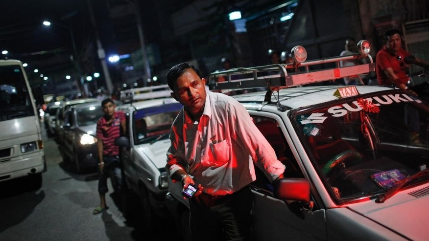 In this Wednesday, Sept. 30, 2015 photo, A Nepalese cab driver waits for his turn to fill fuel on his cab at a fuel pump run by the Nepalese police in Kathmandu, Nepal. Nepal is running out of gasoline and Medical supplies are becoming scarce after an unofficial economic blockade imposed by neighboring India from where Nepal gets almost all its essential supplies. Many Nepalese believe that India is retaliating against their government for approving a new Constitution that is seen by New Delhi as discriminatory to an ethnic Indian community living in Nepal's border districts. (AP Photo/Niranjan Shrestha)