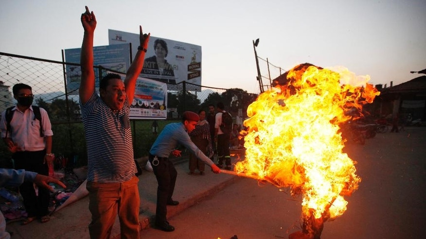 In this Wednesday, Sept. 30, 2015 photo, a Nepalese policeman tries to put off the burning effigy of Indian Prime Minister Narendra Modi during a protest by Nepalese youth in Kathmandu, Nepal. Nepal is running out of gasoline and Medical supplies are becoming scarce after an unofficial economic blockade imposed by neighboring India from where Nepal gets almost all its essential supplies. Many Nepalese believe that India is retaliating against their government for approving a new Constitution that is seen by New Delhi as discriminatory to an ethnic Indian community living in Nepal's border districts. (AP Photo/Niranjan Shrestha)