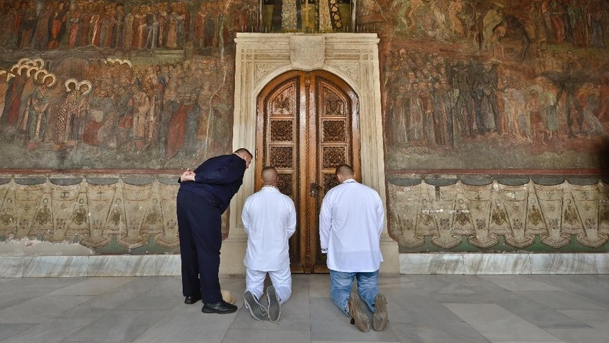 A Romanian gendarme holds his hands behind his back while speaking to men praying outside the door of the Romanian Patriarchy in Bucharest, Romania, Wednesday, Sept. 30, 2015. A religious service was held to mark eight years since Patriarch Daniel began leading the Romanian Orthodox Church. (Andreea Alexandru, Mediafax via AP) ROMANIA OUT