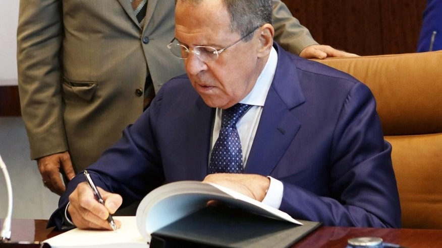 Russia's Foreign Minister Sergey Lavrov signs the United Nations guest book during a meeting with U.N. Secretary-General Ban Ki-moon, Thursday, Oct. 1, 2015 at U.N. headquarters. (AP Photo/Adam Hunger)