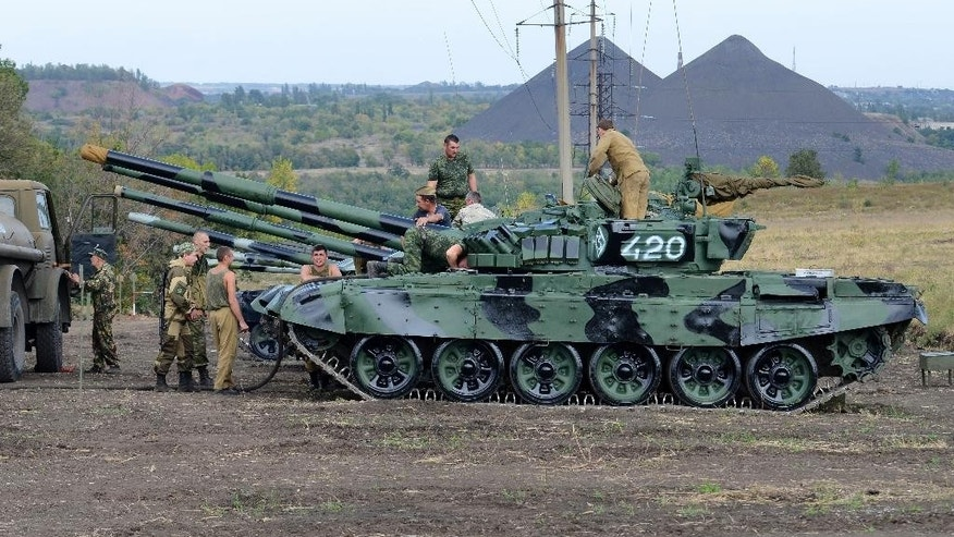 In this photo taken on Monday, Sept. 21, 2015 Russia-backed separatists refuel tanks in a field near Torez, eastern Ukraine. The Ukrainian government said on Thursday, Oct. 1, 2015, it will pull out small-caliber weapons from the war-torn east in two days' time if the cease-fire holds. A military conflict between government forces and Russia-backed separatists in eastern Ukraine has been raging since April 2014, leaving more than 8,000 people dead and 2 million displaced. (AP Photo/Anton Volk)