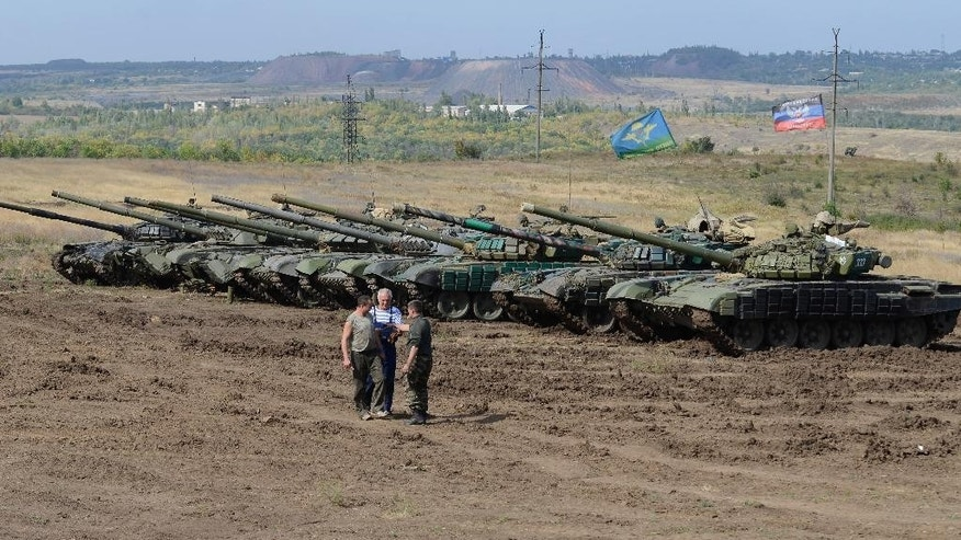 In this photo taken on Monday, Sept.  21, 2015 Russia-backed separatists talk in front of tanks in a field near Torez, eastern Ukraine. The Ukrainian government says Thursday, Oct. 1, 2015 it will pull out small-caliber weapons from the war-torn east in two days' time if the cease-fire holds. A military conflict between government forces and Russia-backed separatists in eastern Ukraine has been raging since April 2014, leaving more than 8,000 people dead and 2 million displaced. (AP Photo/ Anton Volk)