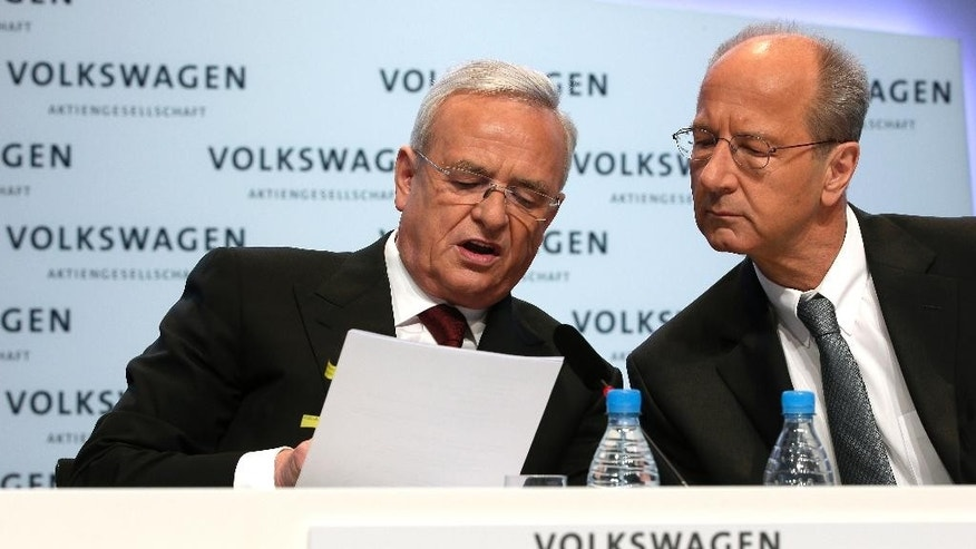 FILE - In this March 13, 2014 file photo then Volkswagen CEO Martin Winterkorn, left, and CFO Hans Dieter Poetsch, right, talk prior to the company's annual press conference in Berlin, Germany. (AP Photo/Michael Sohn, file)