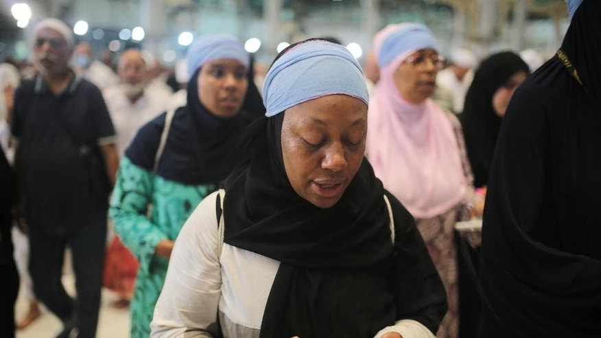"In this Monday, Sept. 21, 2015 photo, Shahidah Sharif circles the Kaaba, the cubic building at the Grand Mosque in the Muslim holy city of Mecca, Saudi Arabia. As Sharif, an African-American Muslim, joined millions of fellow pilgrims from around the world on the hajj this year, she felt a renewed connection. To her own ""blackness,"" she says, but also to humanity as a whole. (AP Photo/Mosa'ab Elshamy)"