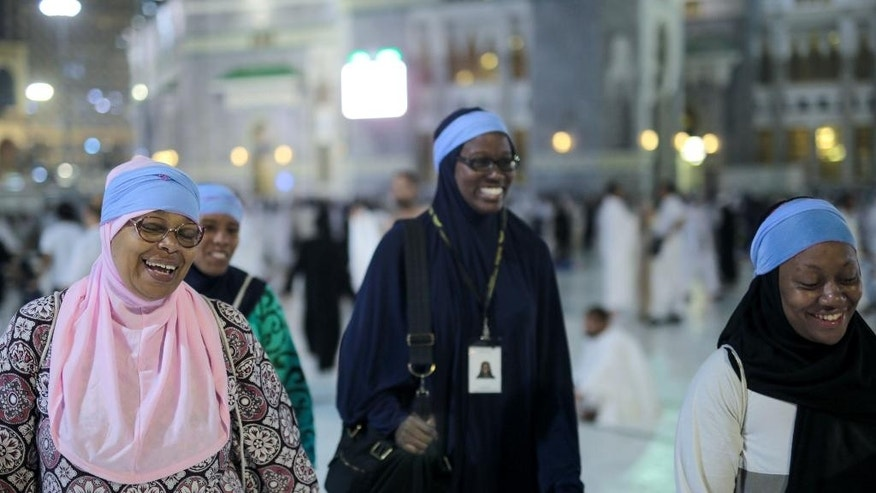 """In this Monday, Sept. 21, 2015 photo, American Muslims Zainab Nasir, left, Shahidah Sharif, Jamila Rashid, second left, and an unidentified friend walk outside the grand mosque on their way to circle the Kaaba, the cubic building at the Grand Mosque in the Muslim holy city of Mecca, Saudi Arabia. For American black Muslims, this year brought a significant landmark, the 50th anniversary of Malcolm X's death. A year before his assassination, Malcolm X underwent a transformative experience on hajj, seeing the potential for racial co-existence after witnessing, as he wrote, pilgrims """"of all colors displaying a spirit of unity and brotherhood."""" (AP Photo/Mosa'ab Elshamy)"""