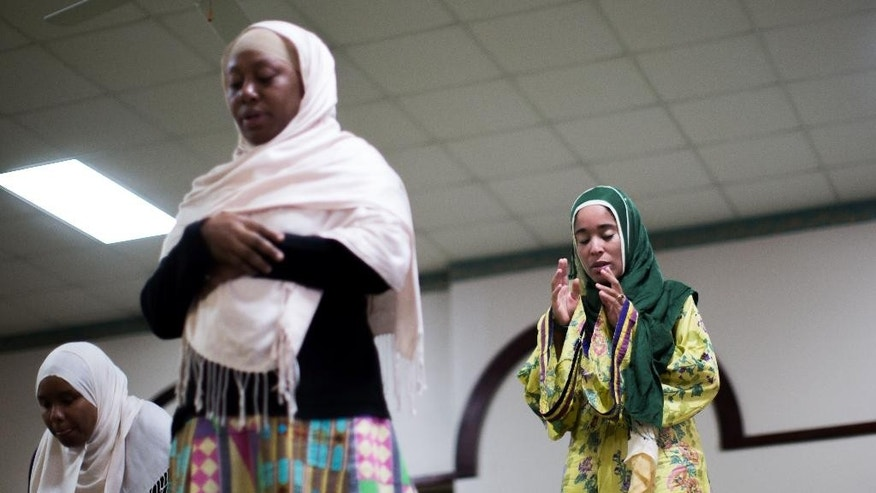 In this Aug. 30, 2015 photo, Yaqutullah Ibraheem Muhammad, right, Shahidah Sharif, center, and an unidentified woman pray together during Sunday prayers at the Atlanta Masjid of Al Islam mosque in Atlanta. Members of the mosque gathered to celebrate a group of pilgrims who will make the annual hajj pilgrimage to the holy city of Mecca. (AP Photo/Branden Camp)