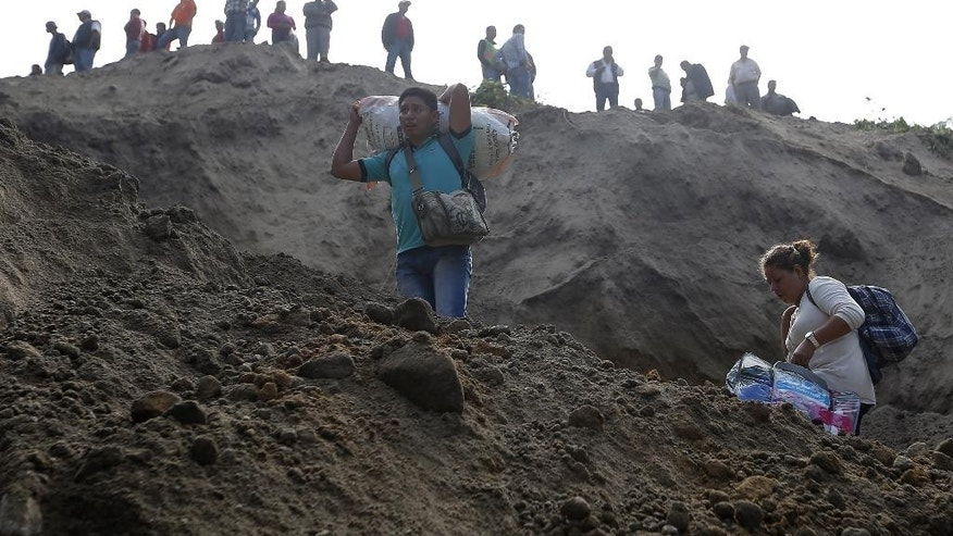 Evacuating residents watch rescue efforts after a landslide hit Santa Catarina Pinula, on the outskirts of Guatemala City, Friday, Oct. 2, 2015. Recent rainfall provoked the landslide, affecting dozens of homes. (AP Photo/Moises Castillo)