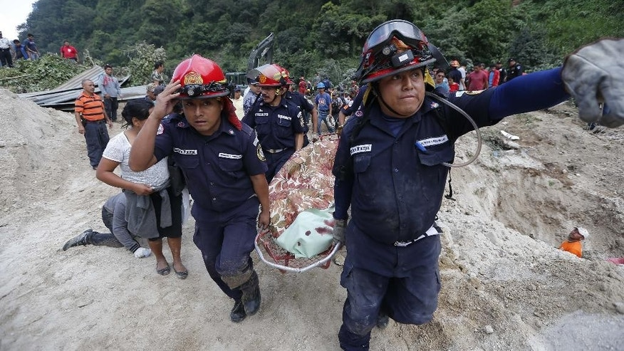 Rescue workers carry a body away from the site of a landslide in Santa Catarina Pinula, on the outskirts of Guatemala City, Friday, Oct. 2, 2015. Recent rainfall provoked the landslide, affecting dozens of homes. (AP Photo/Moises Castillo)
