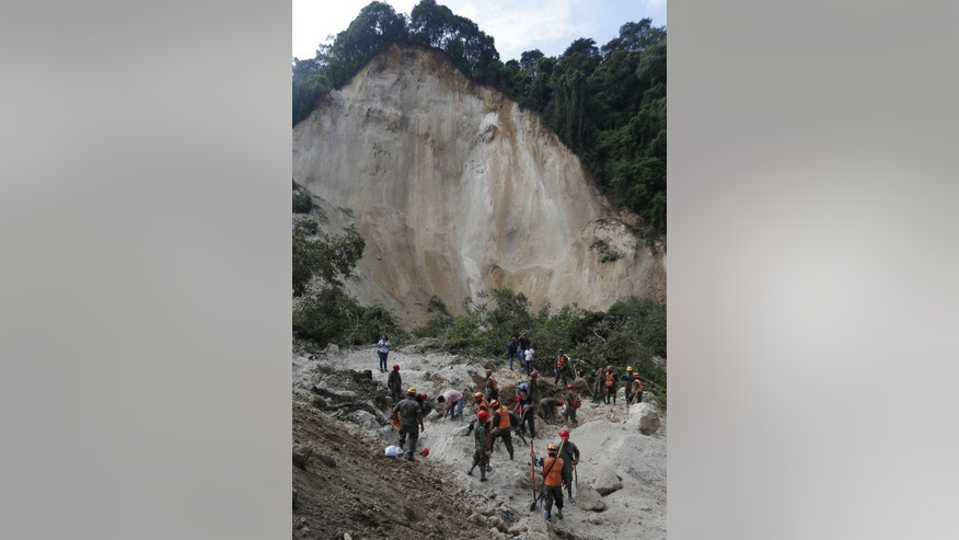 Rescue workers search for survivors and bodies after a landslide in Santa Catarina Pinula, on the outskirts of Guatemala City, Friday, Oct. 2, 2015. Recent rainfall provoked the landslide, affecting dozens of homes. (AP Photo/Moises Castillo)