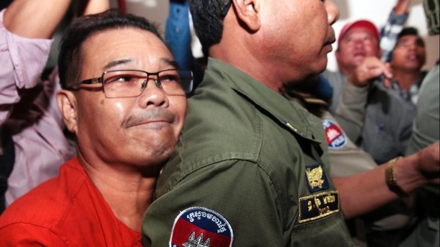 Hong Sok Hour, left, a senator from the opposition Cambodia National Rescue Party, is escorted by riot police officers, center, at Phnom Penh Municipal Court in Phnom Penh, Cambodia, Friday, Oct. 2, 2015. The Cambodian court rejected the opposition senator's request for bail Friday and opened a trial against him on charges that carry penalties of up to 17 years in prison for comments he posted on Facebook. (AP Photo/Heng Sinith)