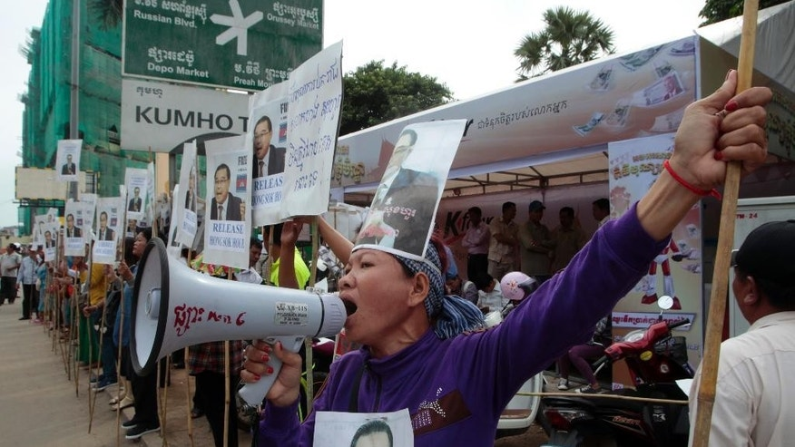Protesters shout slogans with portraits of Hong Sok Hour, a senator from the opposition Cambodia National Rescue Party, in front of Phnom Penh Municipal Court in Phnom Penh, Cambodia, Friday, Oct. 2, 2015. The Cambodian court rejected the opposition senator's request for bail Friday and opened a trial against him on charges that carry penalties of up to 17 years in prison for comments he posted on Facebook. (AP Photo/Heng Sinith)