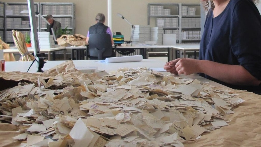 Sept. 10, 2015-  Worker sorts pieces of files of former GDR secret police Stasi in Berlin. The Ministry for State Security used a network of agents and informers to collect details of almost every citizen in East Germany, to better quash dissent. 25 years later, historians are using a method that allows computers to scan pre-sorted shreds and automatically find bits that match to piece information together.