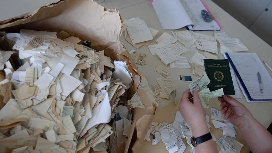In this May 24, 2011 picture, a woman sorts paper fragments at the Government's Institute for checking the former East German Intelligence papers in Berlin, Germany. The Ministry for State Security, better known as the Stasi, used a network of agents and informers to collect details of almost every citizen in East Germany, to better quash dissent. When the communist regime collapsed, Stasi officials tried desperately to destroy the evidence of their totalitarian surveillance apparatus.(AP Photo/Michael Sohn)