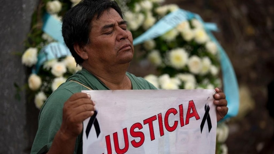 "A man holds a banner that reads in Spanish ""Justice,"" as he pays his respects at a newly erected momument at the place where Julio Cesar Mondragon's body was found, during a march by parents and relatives of 43 missing students and 3 who were killed, in Iguala, Guerrero State, Mexico, Sunday, Sept. 27, 2015. One day after marking the one-year anniversary of the students disappearance with a march in Mexico City, relatives and current Ayotzinapa students visited Iguala to march and place flowers and candles on two new monuments to the students who were killed.(AP Photo/Rebecca Blackwell)"
