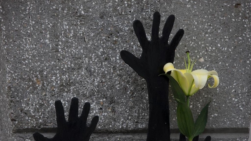 A flower rests next to hands reaching upward on a newly erected monument for two of three students killed on the day 43 others disappeared just over a year ago, in Iguala, Guerrero State, Mexico, Sunday, Sept. 27, 2015. One day after marking the one-year anniversary of the students disappearance with a march in Mexico City, relatives and current Ayotzinapa students visited Iguala to march and place flowers and candles on two new monuments to the students who were killed. (AP Photo/Rebecca Blackwell)