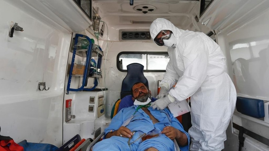 In this picture taken on Wednesday, Sept. 30, 2015, and released by Iranian Students News Agency, ISNA, an Iranian medic attends to a hajj pilgrim who was injured in the deadly stampede during the final days of the annual hajj pilgrimage in Mina near the holy city of Mecca last Thursday, after being loaded to an ambulance upon arrival at Tehran's Imam Khomeini airport, Iran. Iran's death toll from the Saudi hajj disaster has nearly doubled to 464 pilgrims killed, state media reported Thursday, a development that is likely to further strain ties between the Mideast rivals. Iran has led a chorus of international criticism directed at Saudi Arabia's response to the incident, saying its diplomats were not given access to victims until days after the stampede. That's a criticism also levied by Indonesia, the Muslim world's most populous country. (AP Photo/ISNA, Hemmat Khahi)