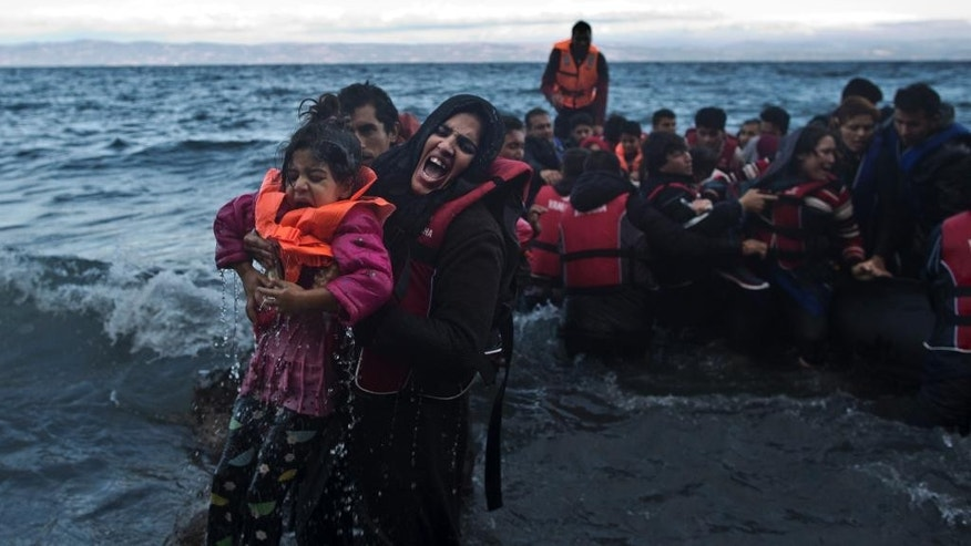 A refugee screams for help after she and her daughter fell into the water after arriving on a dinghy from the Turkish coast to the northeastern Greek island of Lesbos, Friday, Oct. 2 , 2015. The International Organization for Migration says a record number of people have crossed the Mediterranean into Europe this year. (AP Photo/Muhammed Muheisen)
