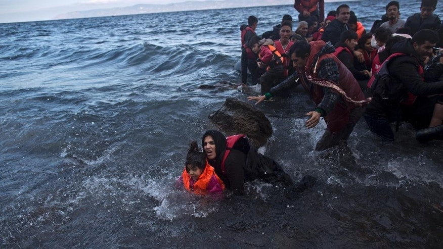 A refugee holding her daughter falls into the water after arriving on a dinghy from the Turkish coast to the northeastern Greek island of Lesbos, Friday, Oct. 2 , 2015. The International Organization for Migration says a record number of people have crossed the Mediterranean into Europe this year. (AP Photo/Muhammed Muheisen)