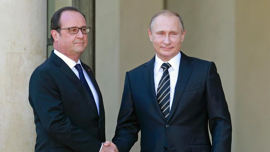 French President Francois Hollande, left, greets his Russian counterpart Vladimir Putin upon his arrival at the Elysee Palace in Paris, France, Friday, Oct. 2 , 2015.  Russian President Vladimir Putin is meeting the leaders of Ukraine, France and Germany in a revived European push to bring peace to eastern Ukraine.The long-awaited summit in Paris on Friday is being overshadowed by international concerns about Russia's military intervention in Syria this week.(AP Photo/Jacques Brinon)