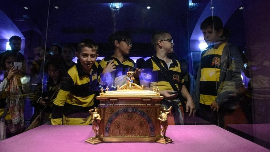 Children look at a gilded silver casket which houses the silver casket used to transport the heart of Queen Marie, the last queen of Romania, from Balchik to Constanta, in Bucharest, Romania, Friday, Oct. 2, 2015. A museum in Bucharest is preparing to send the preserved heart of the last queen of Romania to its final resting place — the castle where she died. Deputy curator of the National History Museum, Cornel Constantin Ilie, told the AP Friday the museum would transfer the heart of Queen Marie in its silver casket to Pelisor castle on Nov. 3. (Andreea Alexandru, Mediafax via AP) ROMANIA OUT