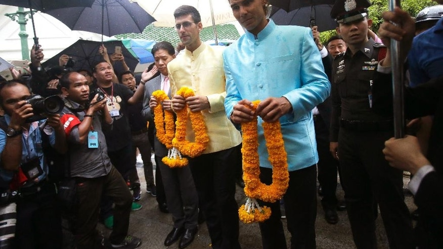 Top tennis players, Novak Djokovic of Serbia, left, and Rafael Nadal of Spain, hold garland to offer for Phra Phrom, the Thai interpretation of the Hindu god Brahma, at the Erawan Shrine in Bangkok, Thailand, Friday, Oct. 2, 2015. Thailand is making special efforts to promote tourism after the Aug. 17 bombing at the shrine. (AP Photo/Sakchai Lalit)