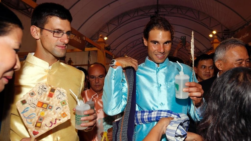 A Thai woman seller gives traditional loincloth to tennis players Rafael Nadal, right, of Spain and Novak Djokovic of Serbia as they visit a fair outside Government House in Bangkok, Thailand Friday, Oct. 2, 2015. Djokovic will face Nadal in the tennis exhibition match in Bangkok to boost confidence in Thailand's safety after a deadly Aug. 17 bombing that left 20 dead in the heart of the capital. (Rungroj Yongrit/Pool Photo via AP)