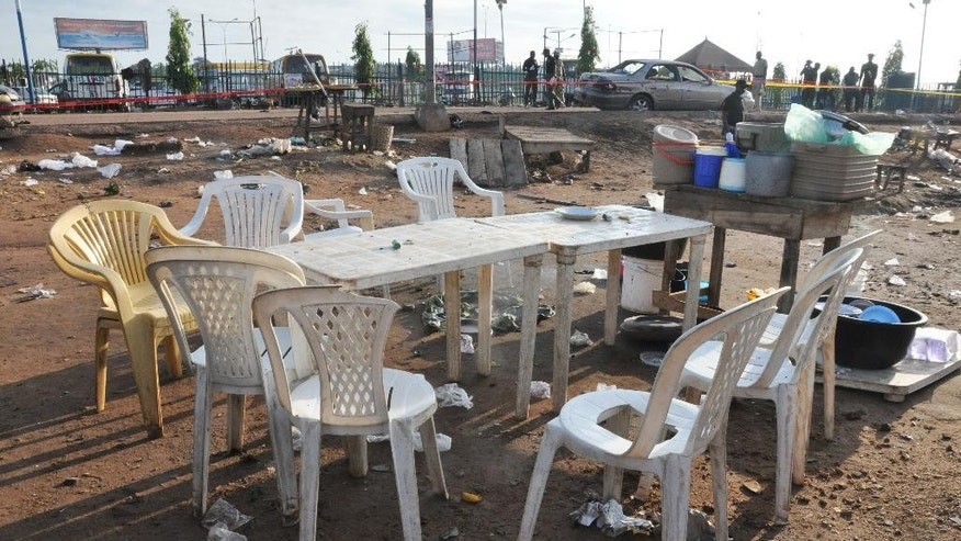 Plastic tables and chairs at the site of a bomb explosion in Abuja, Nigeria, Saturday, Oct. 3, 2015.  Multiple bombs detonated in two locations killing at least 15 people, the National Emergency Management Agency said Saturday, although no group has claimed responsibility the attack has attributes of others by Boko Haram, the home-grown Islamic extremist group. (AP Photo/Gbenga Olamikan)