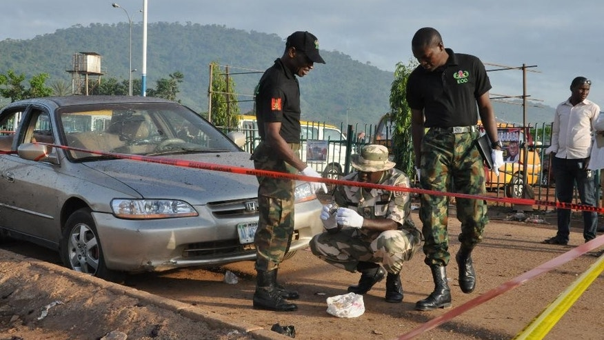 Soldiers gather at the site of a bomb explosion in Abuja, Nigeria, Saturday, Oct. 3, 2015.  Multiple bombs detonated in two locations killing at least 15 people, the National Emergency Management Agency said Saturday, although no group has claimed responsibility the attack has attributes of others by Boko Haram, the home-grown Islamic extremist group.(AP Photo/Gbenga Olamikan)