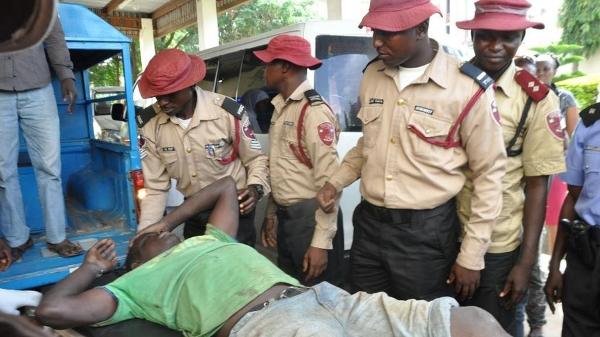 An injured man is helped following a bomb explosion at the site of a bomb explosion in Nyanya outskirt of Abuja, Nigeria, Saturday, Oct. 3, 2015.  Multiple bombs detonated in two locations killing at least 15 people, the National Emergency Management Agency said Saturday, although no group has claimed responsibility the attack has attributes of others by Boko Haram, the home-grown Islamic extremist group.(AP Photo/Gbenga Olamikan)