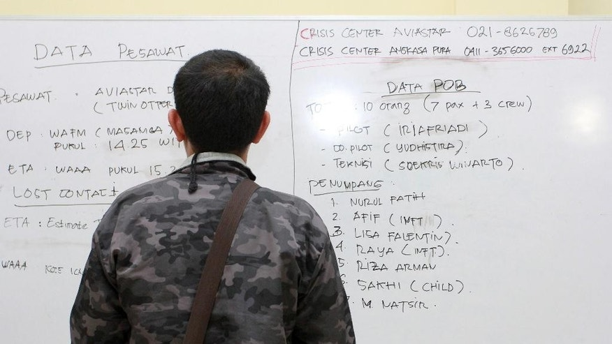 A man inspect a white board with details about a plane that went missing on Sulawesi Island , at the crisis center at Sultan Hasanuddin airport in Makassar, South Sulawesi, Indonesia, Friday, Oct. 2, 2015. Transportation Ministry spokesman Julius Barata said a plane lost contact 11 minutes after taking off in good weather from Masamba in South Sulawesi province. No distress signal was received.  (AP Photo/Masyudi S. Firmansyah)