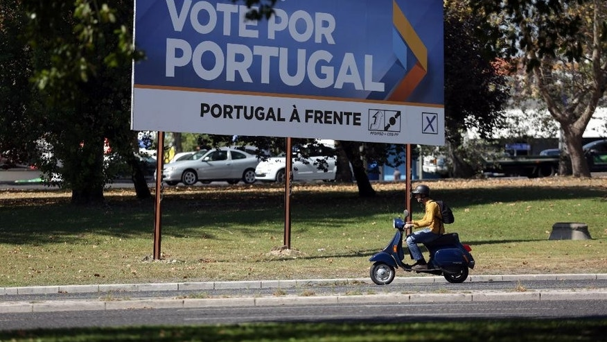 "A scooter drives past an election campaign poster of the ruling center-right coalition ""Portugal Forward"" in Lisbon Thursday, Oct. 1 2015. Poster reads ""Vote for Portugal"". Ahead of Sunday's election, the government is roughly level in polls with the Socialist Party, the main opposition, despite promising more frugality as the economy slowly emerges from a three-year recession. (AP Photo/Armando Franca)"
