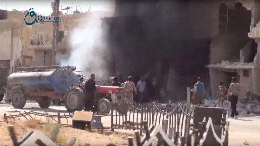 In this Thursday, Oct. 1, 2015, image taken from video provided by the Syrian activist-based media group Qasioun News, which has-been verified and is consistent with other AP reporting, Syrians gather as smoke rises from the rubble of  a building in the aftermath of a Russian airstrike, in Dair al-Asafeer village, rural Damascus, Syria. Russian fighter jets have kept up a sustained rhythm of airstrikes since Wednesday. They carried out 18 sorties in the past 24 hours, including 10 overnight in which seven sites were bombed, the Defense Ministry said Friday. (Qasioun News via AP Video) MANDATORY CREDIT