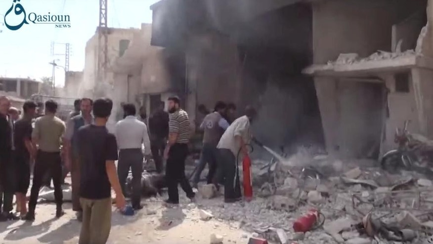 In this Thursday, Oct. 1, 2015, image taken from video provided by the Syrian activist-based media group Qasioun News, which has-been verified and is consistent with other AP reporting, Syrians gather and use a fire extinguisher on the rubble of a building in the aftermath of a Russian airstrike, in Dair al-Asafeer village, rural Damascus, Syria. Russian fighter jets have kept up a sustained rhythm of airstrikes since Wednesday. They carried out 18 sorties in the past 24 hours, including 10 overnight in which seven sites were bombed, the Defense Ministry said Friday. (Qasioun News via AP Video) MANDATORY CREDIT