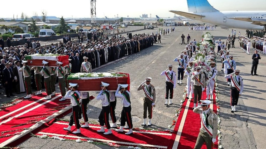 An Honor guard carries the coffins of Iranian hajj pilgrims who were killed in a deadly stampede in Mina near Mecca in Saudi Arabia on September 24, at Mehrabad airport in Tehran, Iran, Saturday, Oct. 3, 2015. The first plane carrying bodies of Iranian pilgrims killed in the hajj stampede in Saudi Arabia arrived in Tehran Saturday, nine days after the disaster that escalated tensions between the two regional rivals. President Hassan Rouhani and other senior officials were at the airport for the arrival of the plane, which carried 104 bodies. (AP Photo/Ebrahim Noroozi)