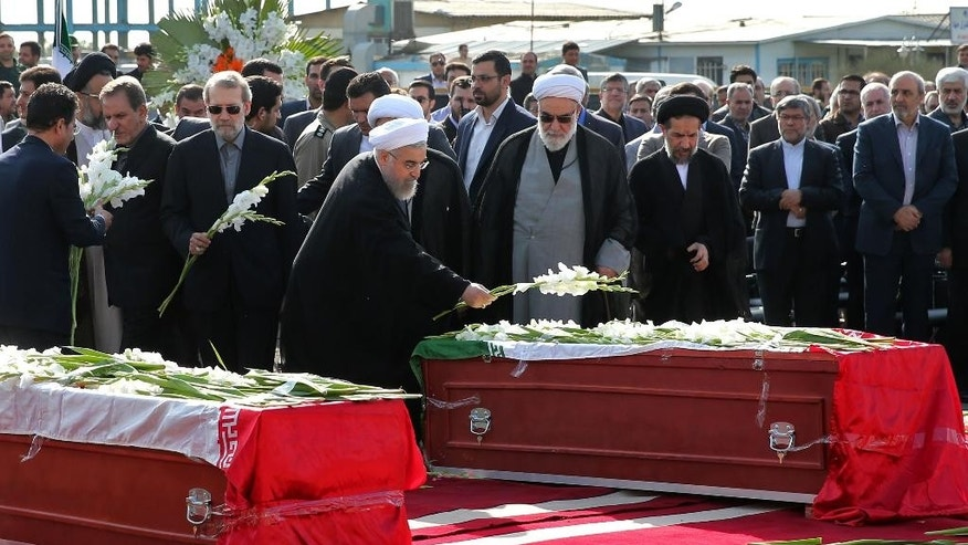 Iran's president Hassan Rouhani, center, places flower on the coffin of a dead hajj pilgrim who was killed in a deadly stampede in Mina near Mecca in Saudi Arabia on September 24 at Mehrabad airport in Tehran, Iran, Saturday, Oct. 3, 2015. The first plane carrying bodies of Iranian pilgrims killed in the hajj stampede in Saudi Arabia arrived in Tehran Saturday, nine days after the disaster that escalated tensions between the two regional rivals. President Hassan Rouhani and other senior officials were at the airport for the arrival of the plane, which carried 104 bodies. (AP Photo/Ebrahim Noroozi)