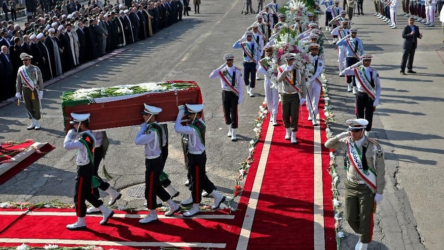 An honor guard carries coffins of Iranian hajj pilgrims who were killed in a deadly stampede in Mina near Mecca in Saudi Arabia on September 24, at Mehrabad airport in Tehran, Iran, Saturday, Oct. 3, 2015. The first plane carrying bodies of Iranian pilgrims killed in the hajj stampede in Saudi Arabia arrived in Tehran Saturday, nine days after the disaster that escalated tensions between the two regional rivals. President Hassan Rouhani and other senior officials were at the airport for the arrival of the plane, which carried 104 bodies. (AP Photo/Ebrahim Noroozi)