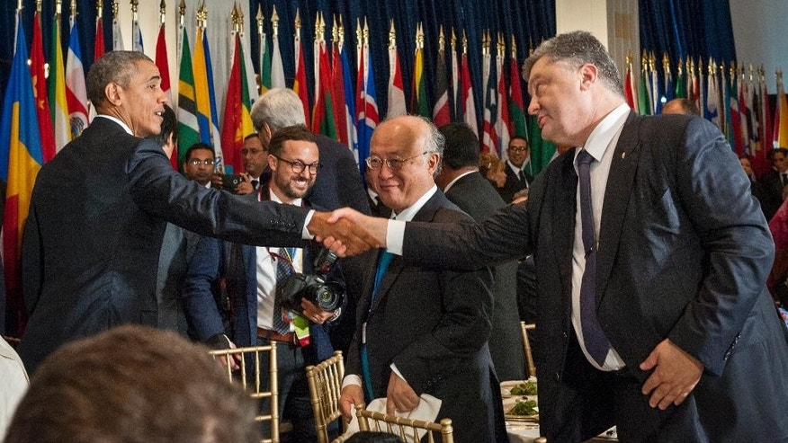In this photo provided by the United Nations on Monday, Sept. 28, 2015, United States President Barack Obama, left, and Ukraine President Petro Poroshenko, right, exchange handshakes in front of Yukiya Amano, center right, Director-General of the International Atomic Energy Agency, at a luncheon for world leaders during the 70th annual United Nations General Assembly at U.N. headquarters.  (Kim Haughton/United Nations via AP)